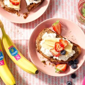 Vollkornbrot mit fettfreiem Hüttenkäse, Chiquita Bananen, Erdbeeren, Blaubeeren und Sesamsamen